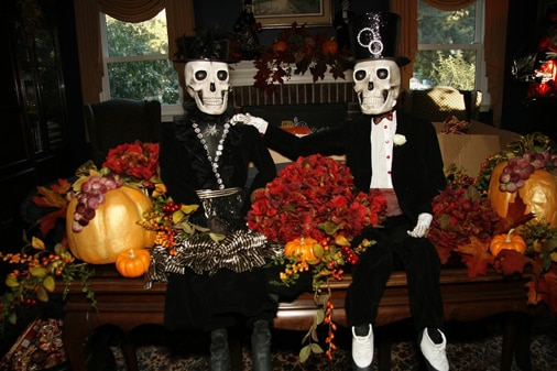 Cute Halloween skeletons displayed with fall flowers and pumpkins