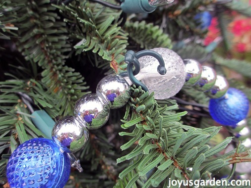 Use plastic clips to attach garland to the tree