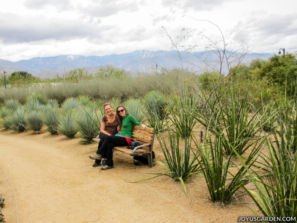 two women sitting on a bench in a desert garden with mountains in the background