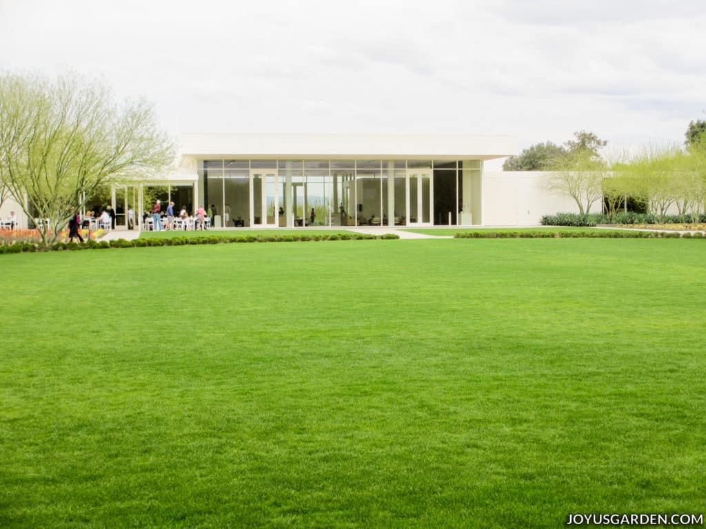 a mid-century modern building at sunnylands center & gardens with a bright green lawn in the foreground