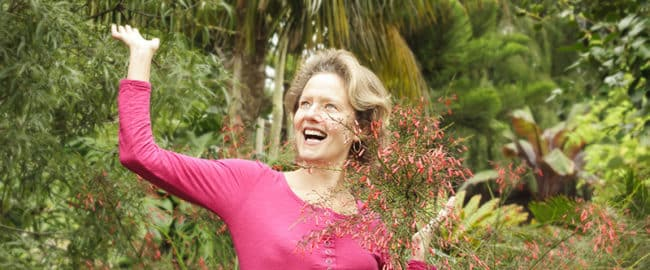 Nell Foster smiling next to a firecracker plant in bloom