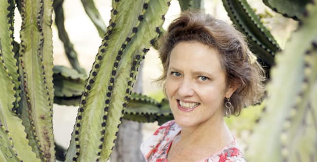 Gardening blogger Nell Foster under a big cactus