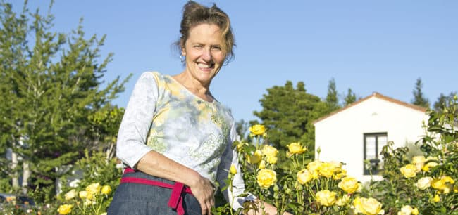 gardening blogger nell foster wearing a half apron standing next to gorgeous yellow roses in bloom