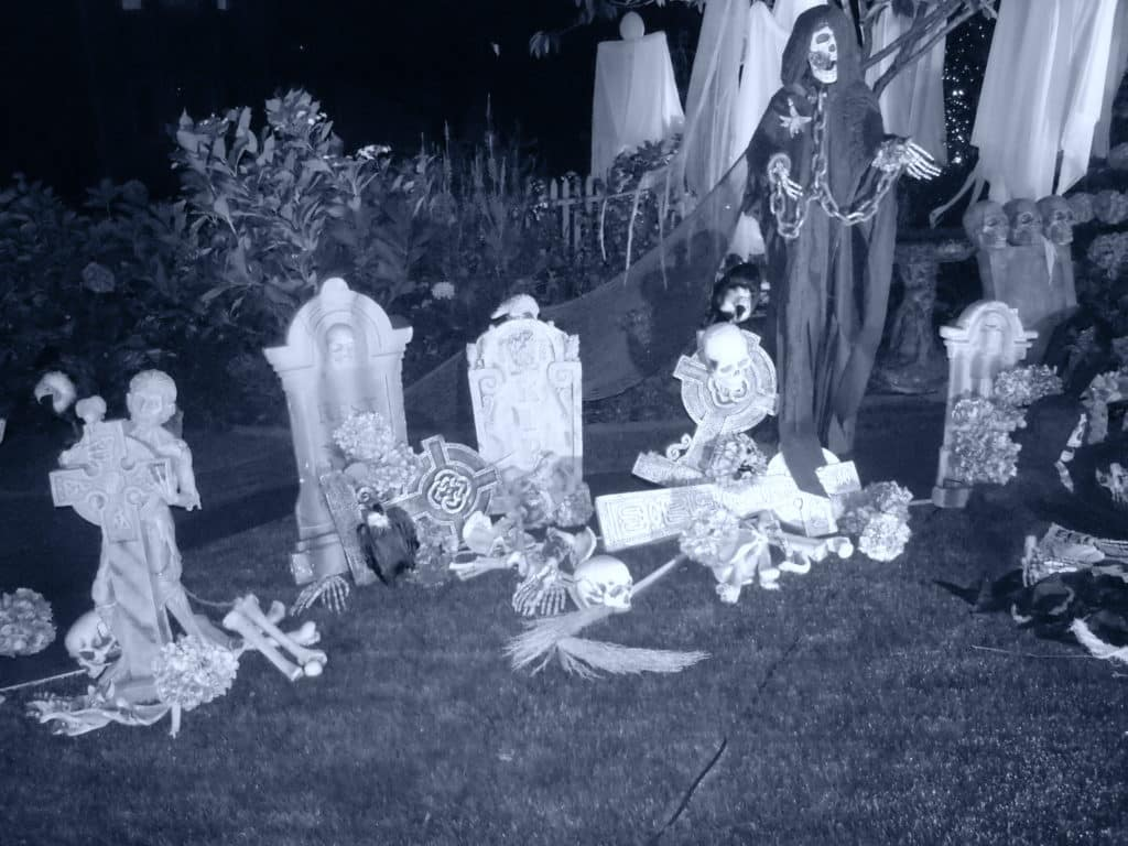 black and white photo of halloween decor, skulls, tombstones in a front yard