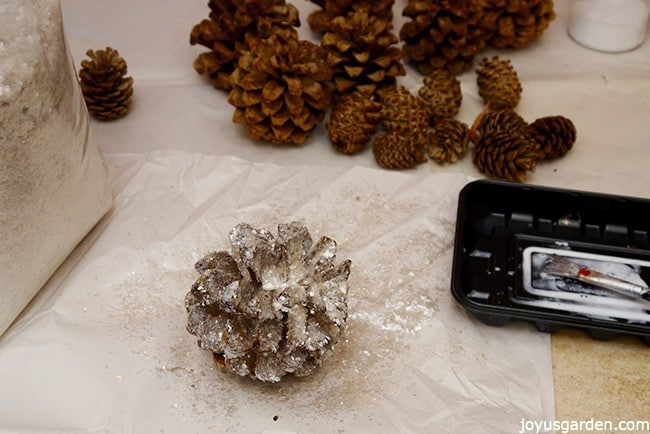 1 crystal glittered pine cones sits in front of a tray with a brush & glue, plain pine cones, & a canister of glitter there is a large bag of glitter next to the pine cone