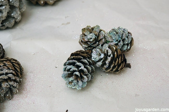 pine cones glittered with iridescent glitter sit on a piece of white paper