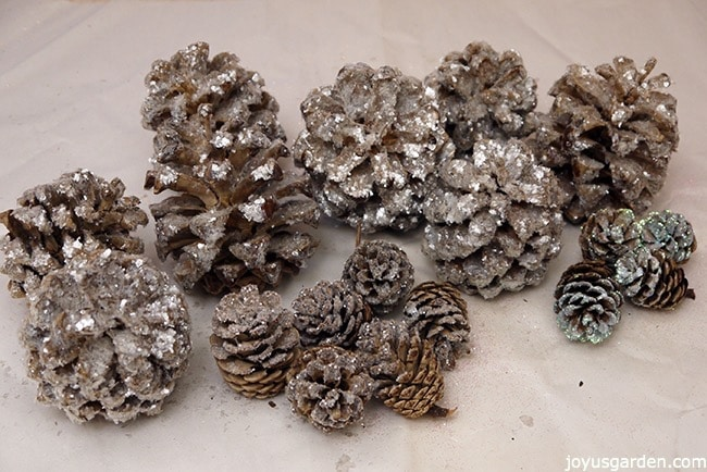 a grouping of many small to medium sized sparkly, crystal glitter pine cones