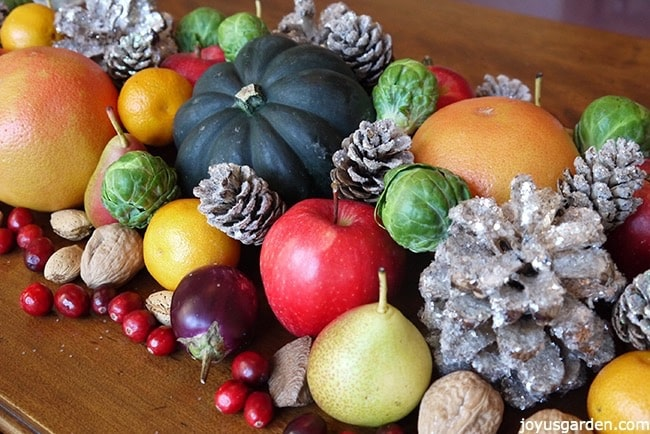 a christmas table centerpiece with fruits vegetables nuts & glitter pinecones