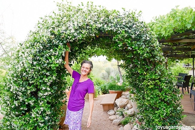 Nell Foster In A Purple Top Stands Underneath An Arch Covered With Star Jasmine Full