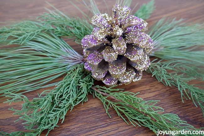 a pine cone glittered with gold & purple glitters sits on evergreen branches