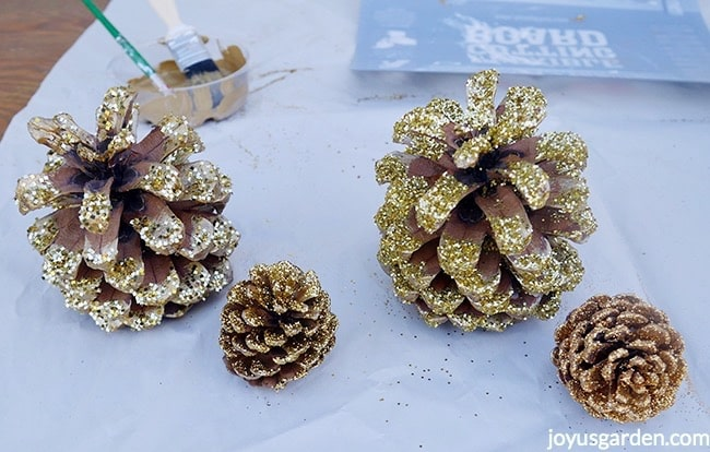 2 sizes of pine cones are painted gold & glittered with 4 different types of gold glitter