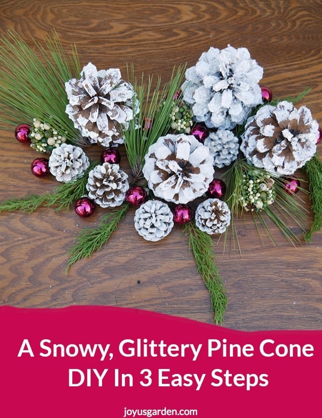 white glittered pine cones sit on a table decorated with glass balls & evergreen branches the text reads A Snowy, Glittery Pine Cone DIY In 3 Easy Steps