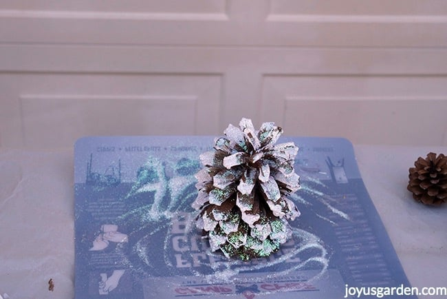 A pine cone brushed with white paint & sprinkled with glitter sits on a flexible cutting board