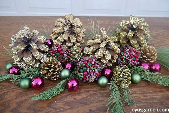 gold glittered pine cones, burgundy & green balls, & evergreen branches sit on a table