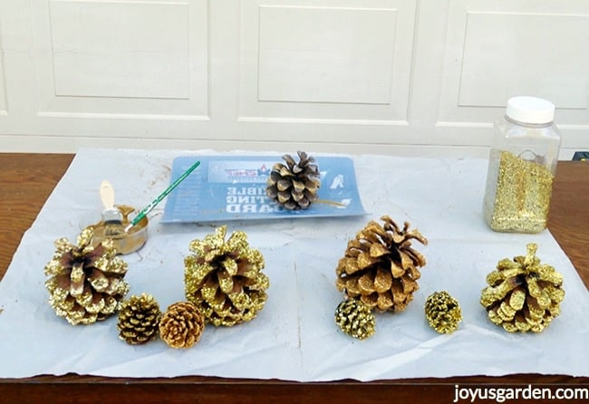 gold glittered pine cones, a jar of gold glitter, a saucer with gold paint & 2 brushes & a flexible cutting board sit on a piece of paper on a table
