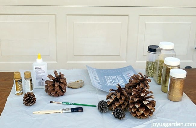 Pine cones, 4 types of gold glitters, school glue, metallic paints, 2 brushes & a flexible cutting board sit on a work table