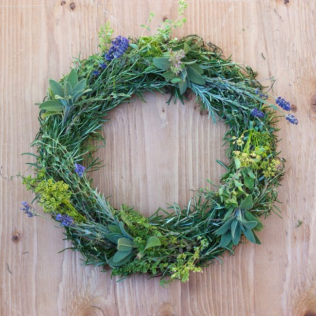a wreath made of herbs accented with lavender flowers