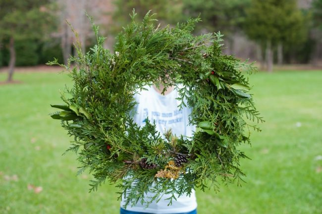 a round evergreen wreath being hold by a woman