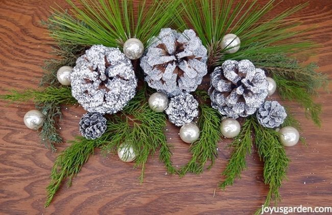 A decoration of silver glittered pine cones with pearlescent balls & fresh evergreen branches sit on a table.
