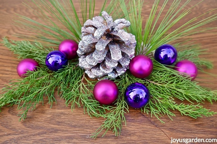 Close up of a silver & pink glittered pine cone adorned with hot pink & purple balls & fresh evergreen branches