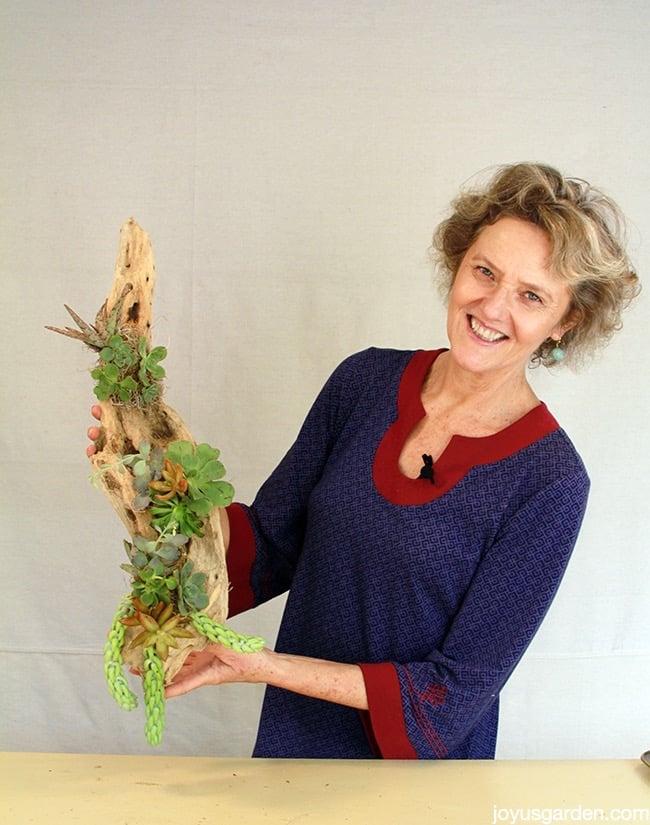 nell foster holding a long succulent & driftwood arrangement