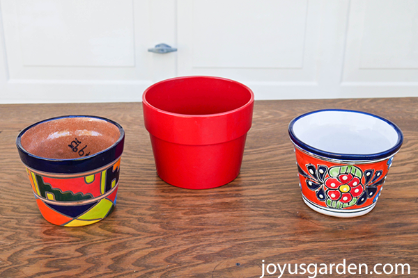 2 small colorful talavera pots sit on a table with a small colorful red pot in between