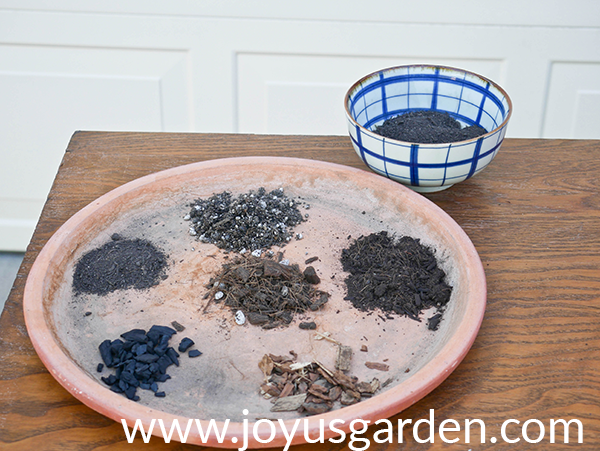 a large terra cotta saucer sits on a table with 6 different soils & amendments in it a blue & white bowl sits behind it