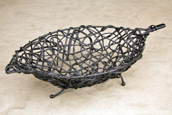 a modern black oval-shaped basket with wire feet sits on a cement patio