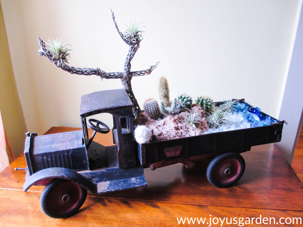 a dish garden with cacti, air plants, pumice stone & glass chips created in an antique dump truck sits on a table