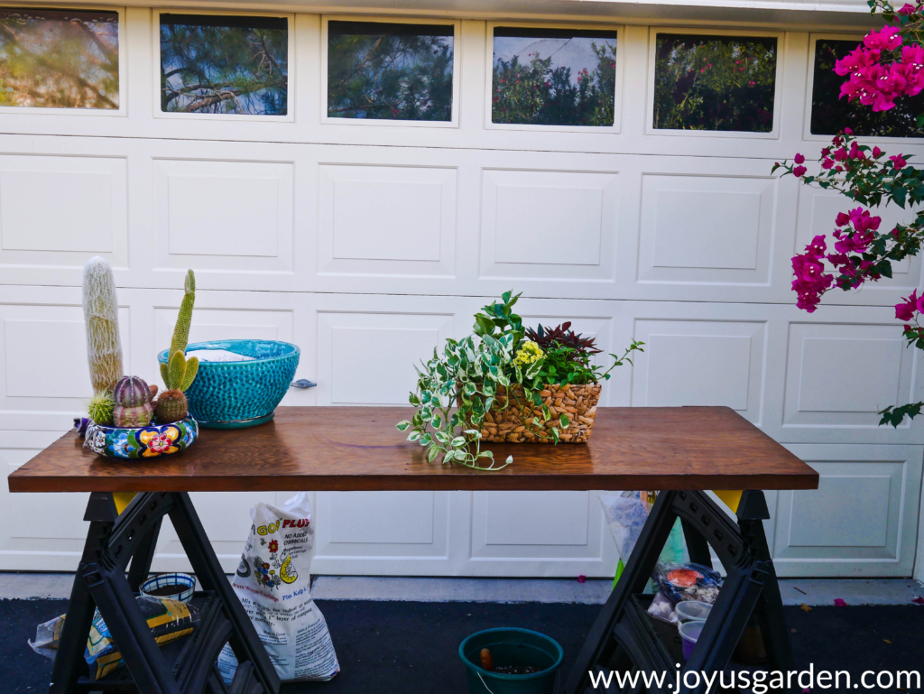 a work table outside a garage holds 2 dish gardens & a glazed turquoise pot