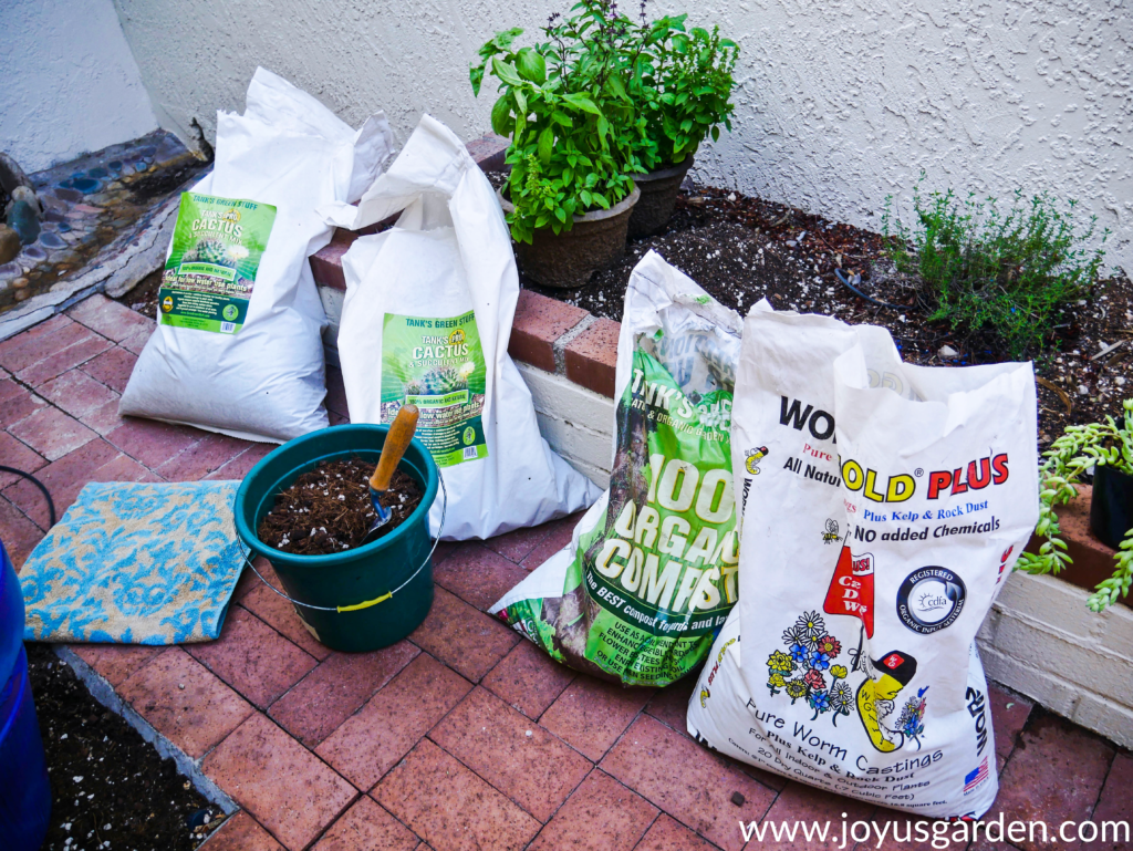 4 bags of soil mix & amendments lined up on a brick walkway