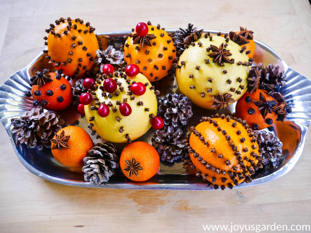 a silver tray is filled with citrus fruits adorned with cloves star anise star anise & cranberries along with glittered pine cones