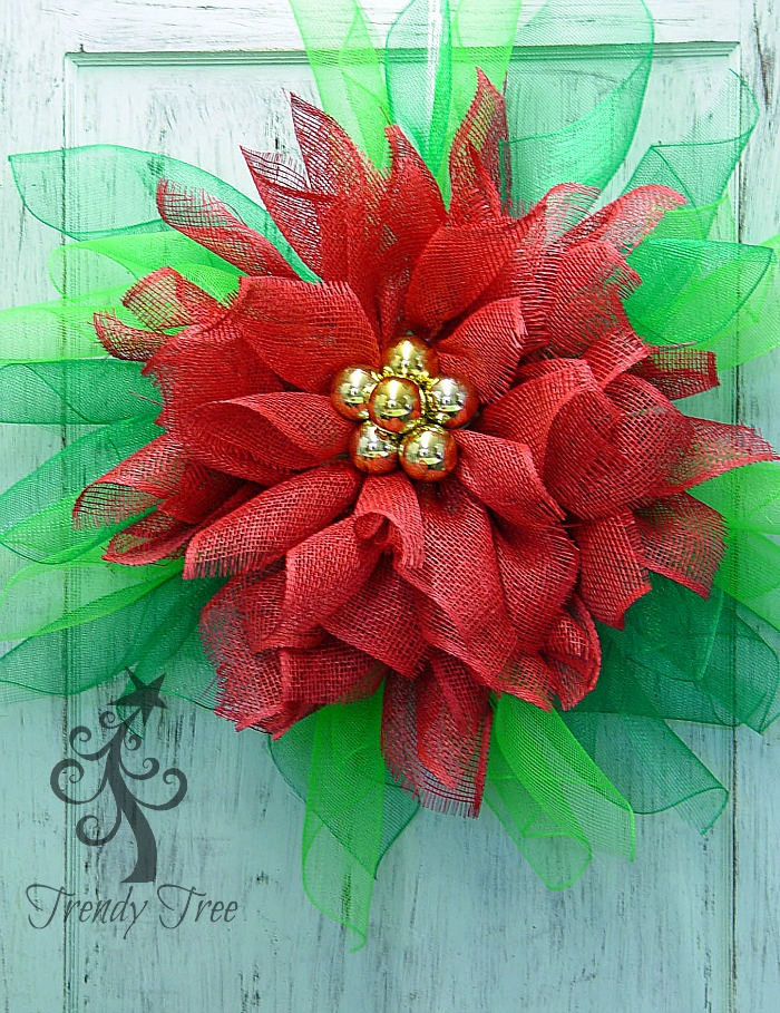 close up of a green mesh & red burlap poinsettia on a door