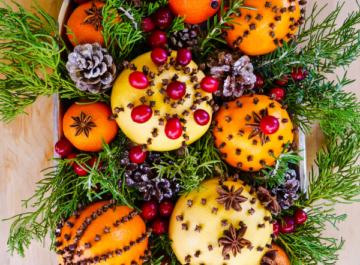 a silver tray for holiday decor is full of spice adorned citrus fruits, evergreen & rosemary springs & cranberries