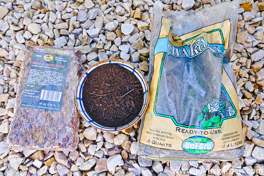 coco fiber in a block a bowl of compost & a bag of charcoal lay on a pebble walkway