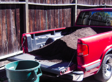 the back of an empty green barrel sits next to a red truck filled with soil amendments