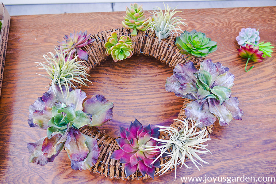 a vine wreath with faux succulents in the process of being created