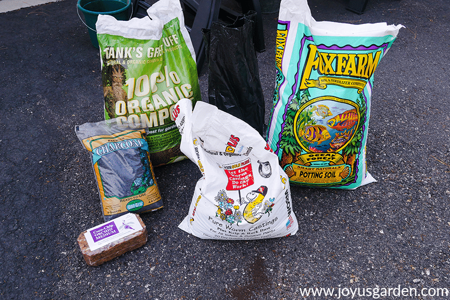 bags of ingredients to make up a soil mix for planting baby rubber plants sit in a driveway