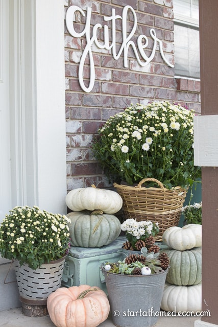 a front porch decorated for fall in green white & peach. a sign reads gather