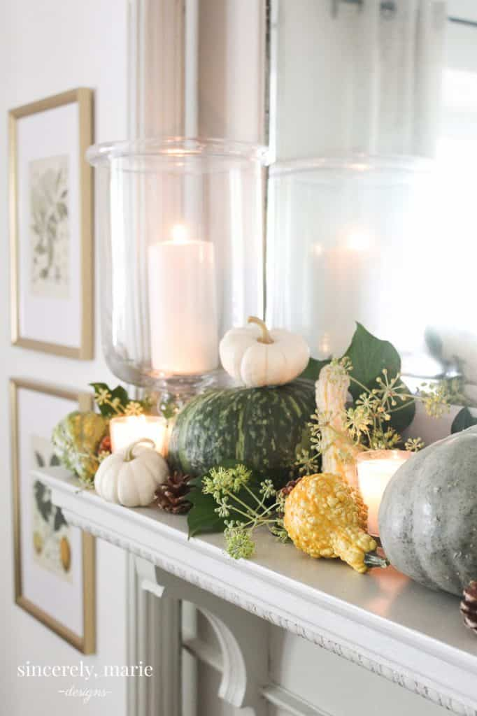 a mantle piece decorated for fall in greens & whites with pumpkins eucalyptus pine cones & candles