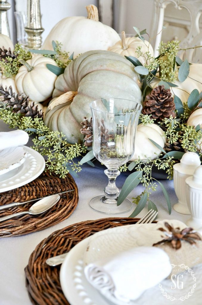 close up of a fall table centerpiece decorated in soft green & white tones with pumpkins pine cones & eucalyptus