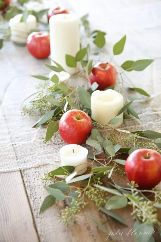 a fall center piece with apples eucalyptus & candles