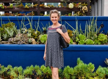 nell foster stands in front of beautiful & colorful mixed succulents gardens
