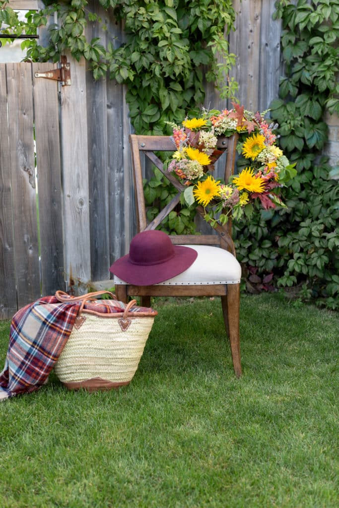 a colorful fresh floral fall wreath hangs off a chair. a red hat & a basket sit next to the wreath