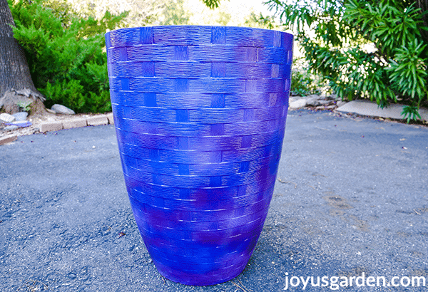 a tall blue vase type pot sits in a driveway
