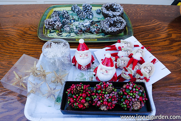 2 trays full of christmas ornamentation sit on a wooden table