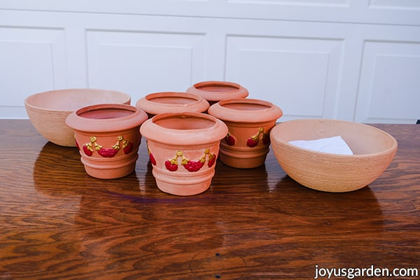 2 terra cotta bowls & 5 terra cotta pots painted  with red & gold sit on a table