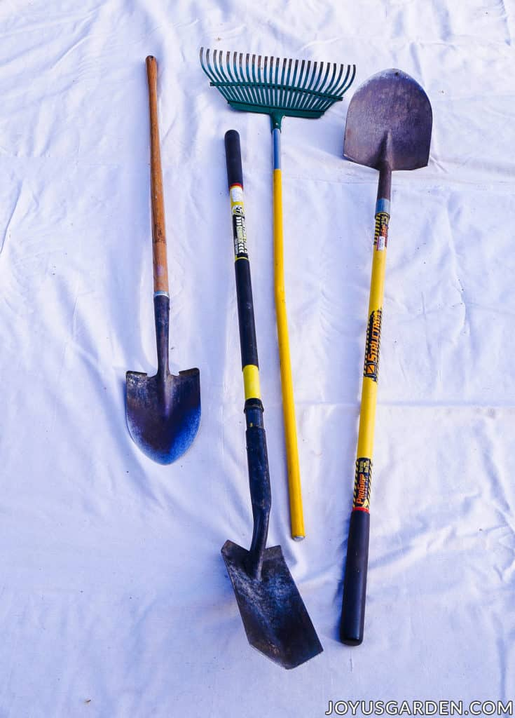 3 different shovels & a rake used for gardening