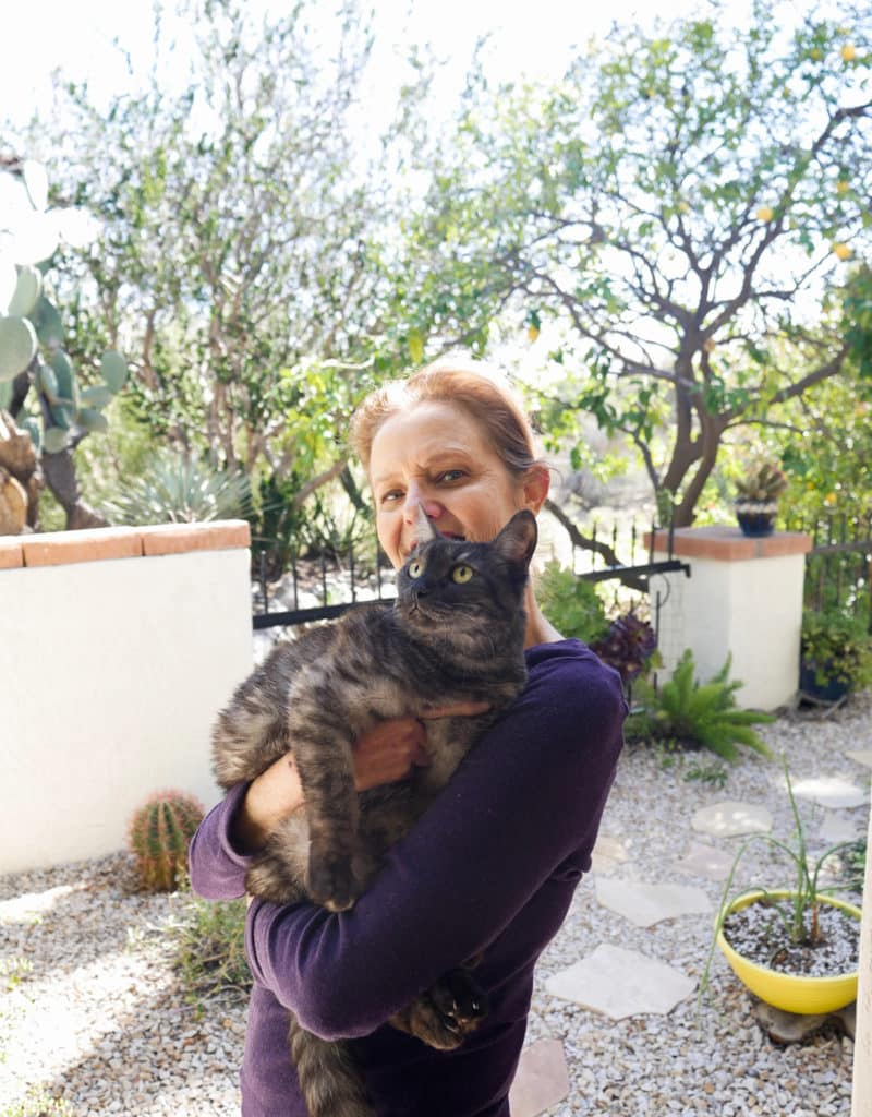 nell foster holds her grey striped kitty Riley in her garden
