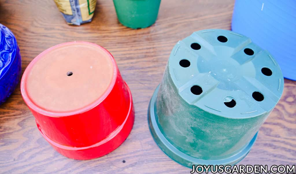 a red ceramic & a green grow pot are turned upside down on a work table